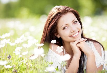 young brunette laying on her stomach in a field of flowers.