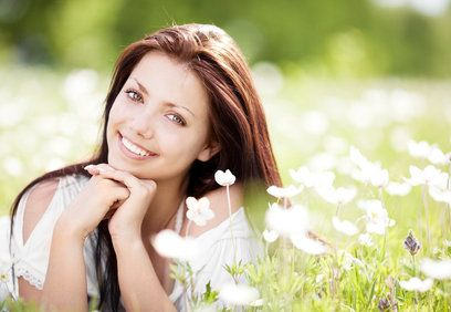 Pretty Caucasian woman in daisy field, smiling with hands clasped under chin